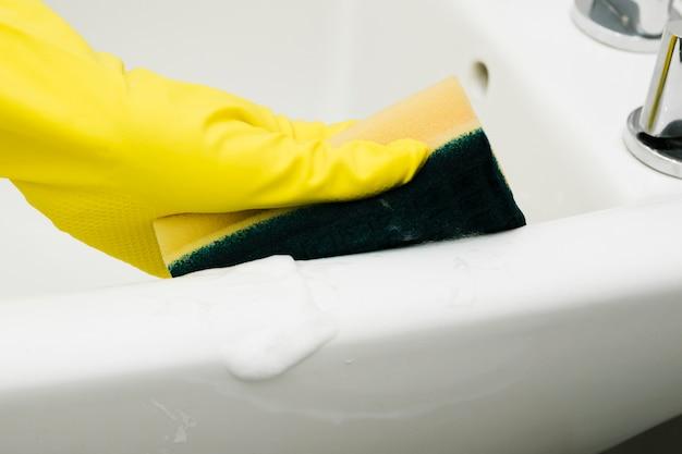 Chiuda sul lavandino di pulizia dell'uomo con la spugna