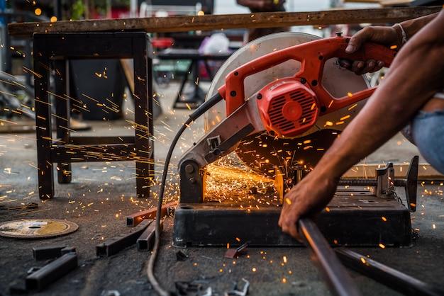 Chiuda sul lavoratore che utilizza l'acciaio di taglio a macchina