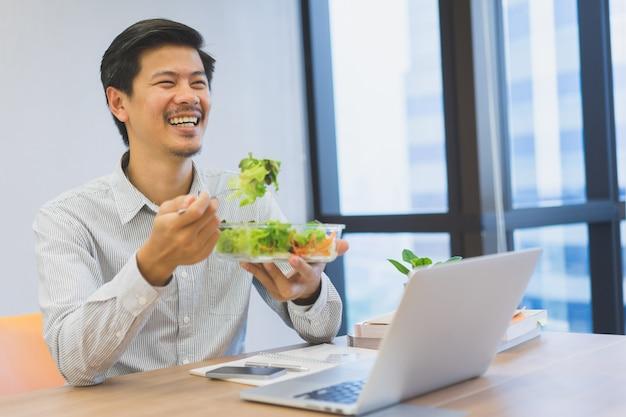 Chiuda sul mangiatore di uomini asiatico adulto che mangia l'insalata organica mentre guardano i media sul computer portatile nell'intervallo di pranzo