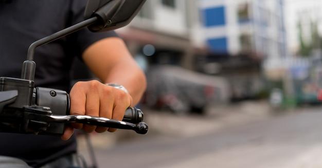 Chiuda sul manubrio di tocco della mano dell'uomo del motociclista per la guida del motociclo alla strada