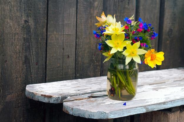 Chiuda sul mazzo dei wildflowers su un legno
