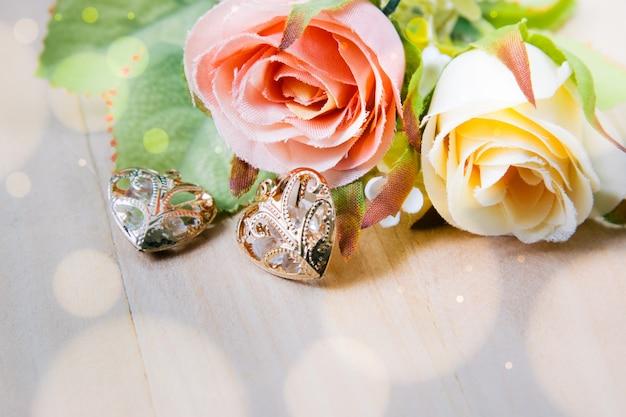 Chiuda sul mazzo le rose e la forma del cuore su fondo di legno, sull'annata rosa e sul concetto del biglietto di s. valentino.