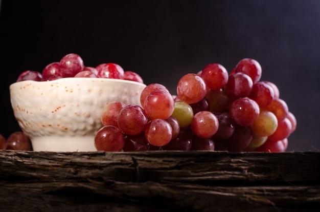 Chiuda sul mazzo maturo dell'uva rossa su una vecchia superficie di legno. foto lunatica scura dell'uva rosa in una ciotola.