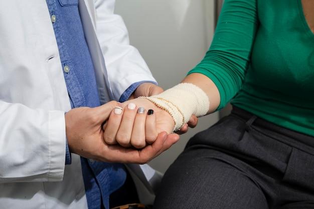 Chiuda sul medico che controlla il braccio bendato
