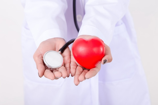 Chiuda sul medico che tiene il cuore e lo stetoscopio rossi. concetto per la salute