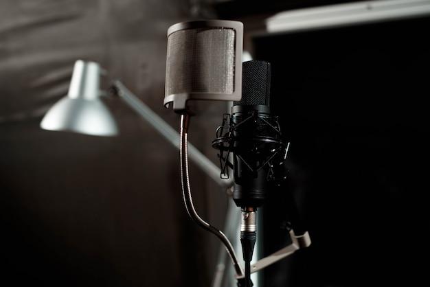 Chiuda sul microfono del condensatore dello studio con il filtro a schiocco