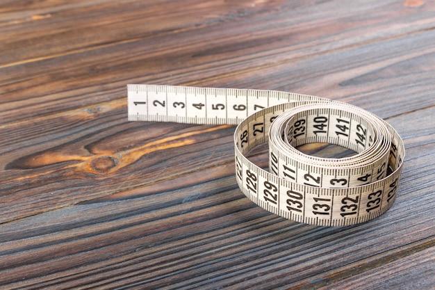 Chiuda sul nastro di misurazione del sarto su legno