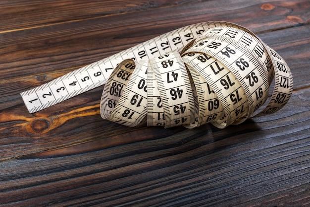Chiuda sul nastro di misurazione del sarto sulla tavola di legno.