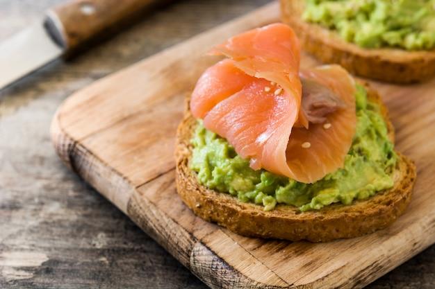 Chiuda sul pane tostato dell'avocado con i salmoni freschi sulla tavola di legno