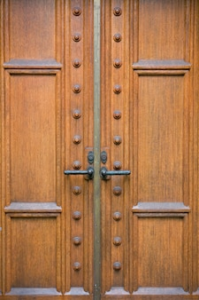 Chiuda sul particolare della porta antiquata e di legno con le maniglie decorate del ferro