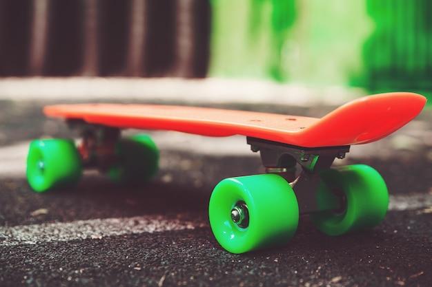 Chiuda sul pattino arancio del penny su asfalto dietro la parete verde