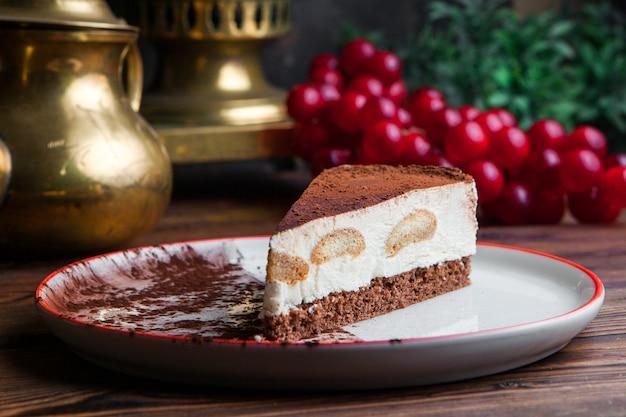 Chiuda sul pezzo di cheesecake su una tavola di legno