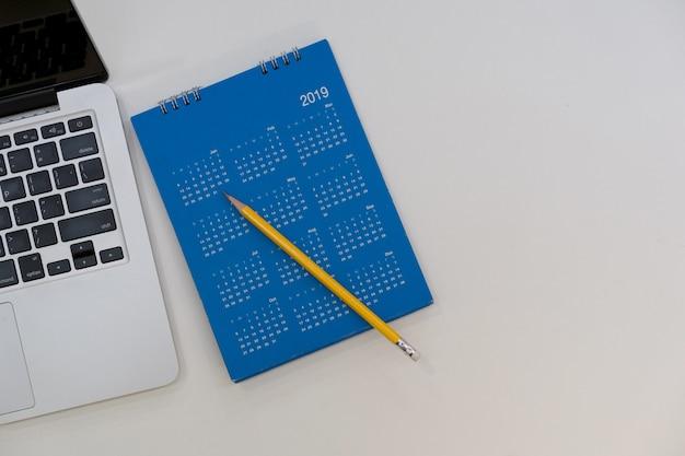 Chiuda sul piano posano il calendario 2019 con il computer portatile sulla tavola bianca per il concetto del nuovo anno