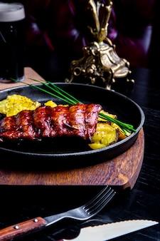 Chiuda sul piatto principale gastronomico con la costata arrostita della carne di maiale e le patate fritte sulla pentola nera. servito su tavola di legno