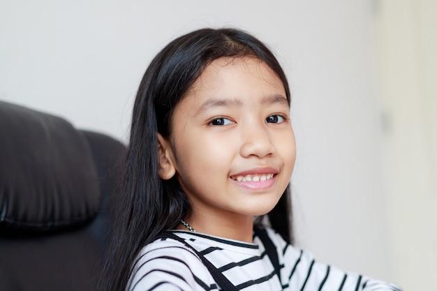 Chiuda sul piccolo sorriso asiatico della ragazza del ritratto con profondità di campo bassa del fuoco selezionato felicità