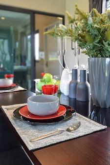 Chiuda sul pranzare insieme moderno sul tavolo da pranzo di legno