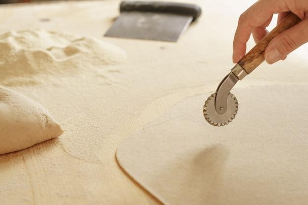 Chiuda sul processo di pasta casalinga del farfalle del vegano. il cuoco usa la taglierina per tagliare l'impasto
