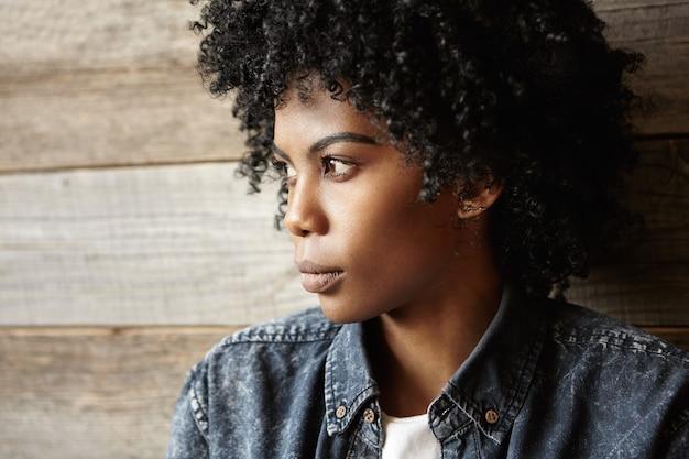 Chiuda sul profilo della ragazza africana alla moda con l'acconciatura afro che indossa la camicia di jeans alla moda