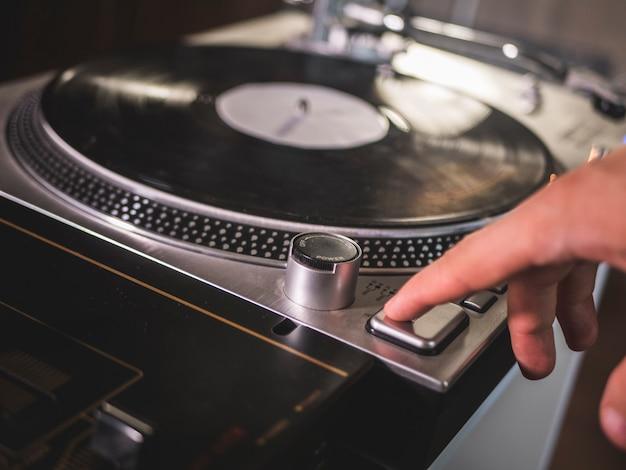 Chiuda sul pulsante di riproduzione di inizio di spinta della mano sul giradischi d'annata del grammofono del giradischi delle annotazioni di vinile