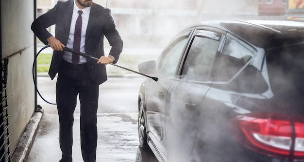 Chiuda sul punto di vista dell'uomo alla moda bello in vestito che pulisce la sua automobile alla stazione di self service di lavaggio manuale dell'automobile