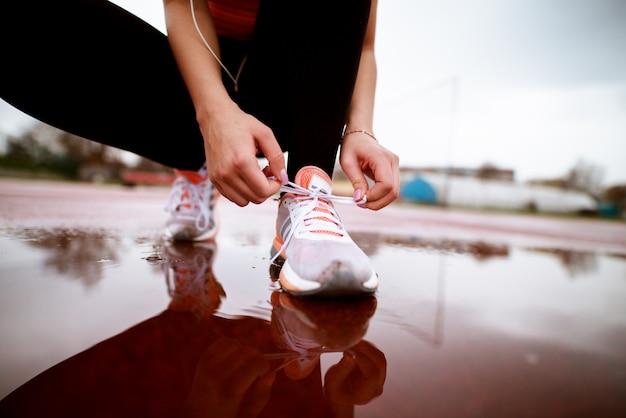 Chiuda sul punto di vista della donna di forma fisica che lega la sua scarpa sinistra sopra lo stagno sulla pista atletica.