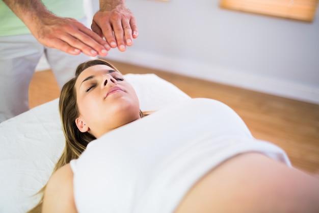 Chiuda sul punto di vista della donna incinta che ottiene il trattamento di reiki