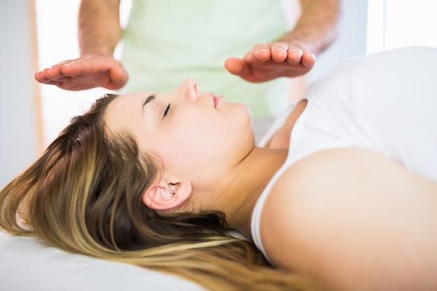 Chiuda sul punto di vista della donna incinta rilassata che ottiene il trattamento di reiki