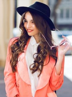Chiuda sul ritratto all'aperto della donna graziosa alla moda in attrezzatura luminosa casuale dell'estate o della primavera. acconciatura riccia bruna. colori luminosi e solari.