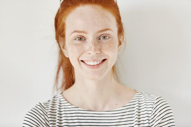 Chiuda sul ritratto altamente dettagliato della studentessa caucasica felice e allegra con sorriso carino, capelli rossi e pelle lentigginosa perfetta e sana che riposa al chiuso dopo le lezioni all'università