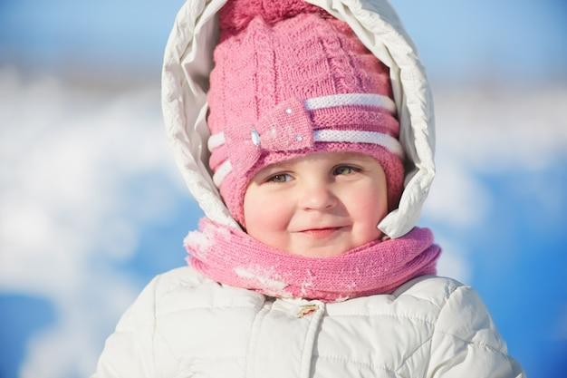 Chiuda sul ritratto del bambino femminile adorabile in vestiti caldi dell'inverno posa contro la neve