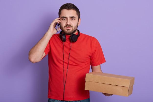 Chiuda sul ritratto del fattorino barbuto serio che porta la maglietta casuale rossa, parlando tramite telefono cellulare con il cliente, tenendo il contenitore di cartone in mani isolate sopra la parete lilla. concetto di consegna.