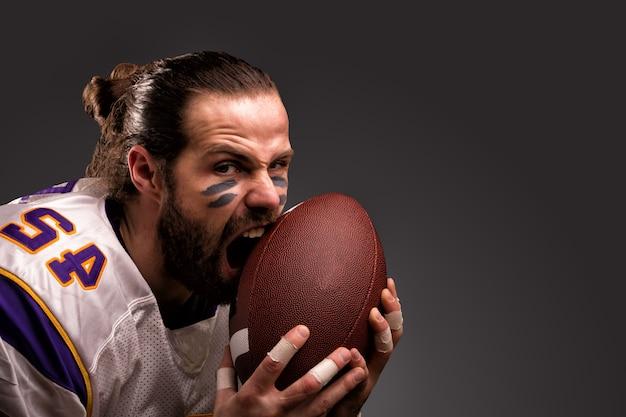 Chiuda sul ritratto del giocatore aggressivo del giocatore di football americano aggressivo che morde la sua palla