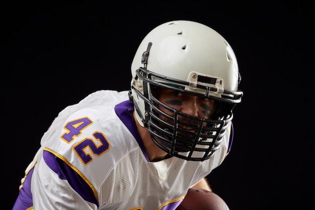 Chiuda sul ritratto del giocatore dello sportivo di football americano nell'azione sul nero. sport .