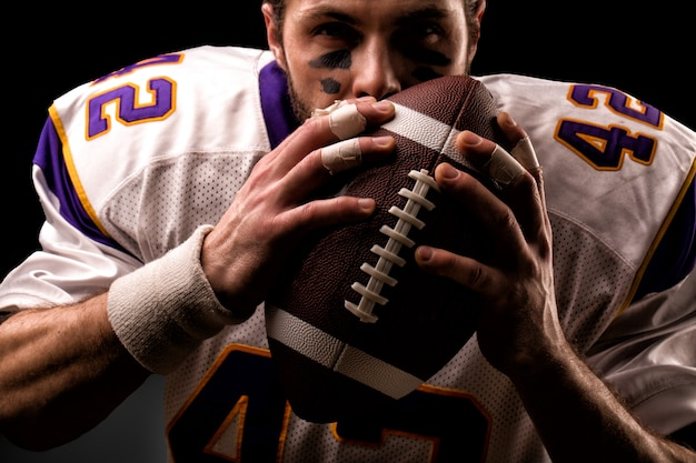 Chiuda sul ritratto del giocatore di football americano che bacia delicatamente la palla