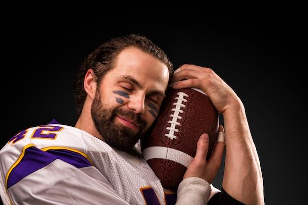 Chiuda sul ritratto del giocatore di football americano che tiene delicatamente la palla