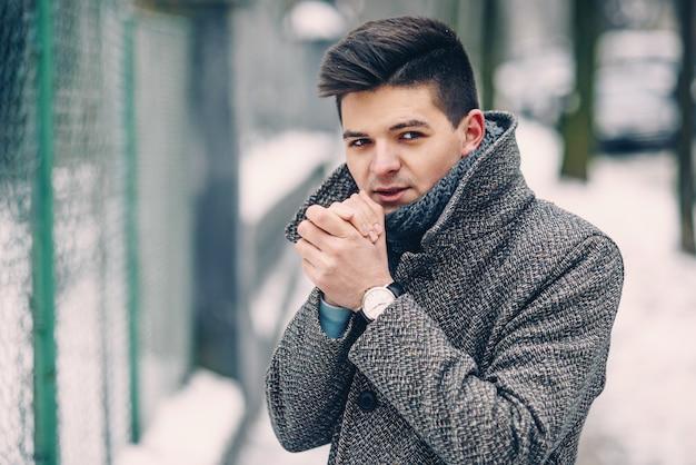 Chiuda sul ritratto del giovane bello in un cappotto caldo con la camminata alla moda dell'orologio dowm la via