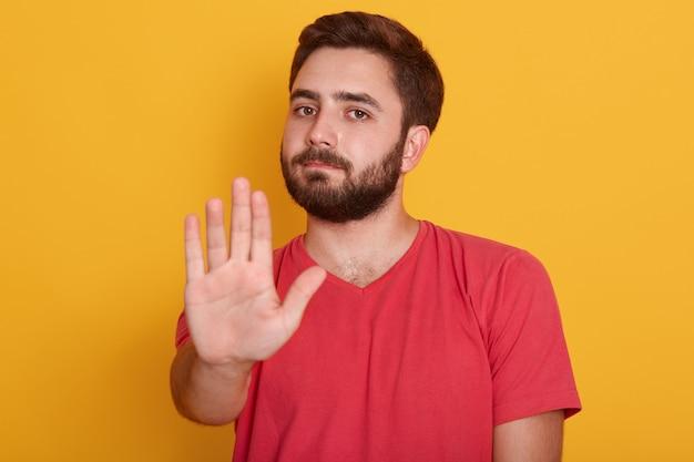 Chiuda sul ritratto del giovane che richiede l'arresto con la sua mano, il tipo bello che porta la maglietta rossa, mostrando il gesto di arresto