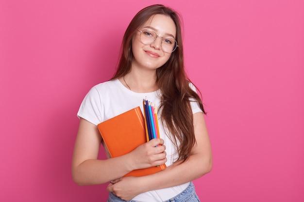 Chiuda sul ritratto del manuale sveglio della tenuta della giovane donna e delle matite colorate, posando nello studio isolato sopra il rosa