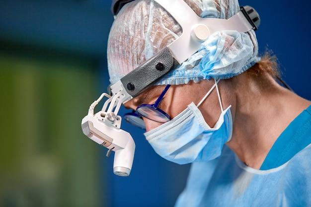 Chiuda sul ritratto del medico chirurgo femminile che indossa la maschera protettiva e cappello durante l'operazione. assistenza sanitaria, educazione medica, concetto di chirurgia.