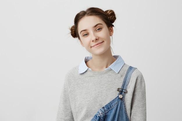 Chiuda sul ritratto del sorriso gentile della ragazza teenager adorabile. brillante donna bruna con i capelli in doppio panino sentirsi bene godendo la sua giovinezza. concetto di bellezza