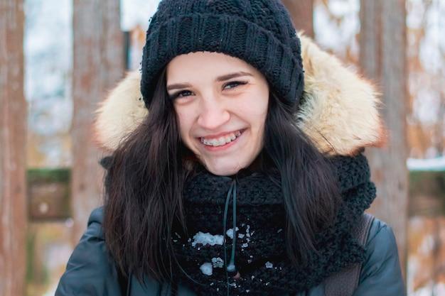 Chiuda sul ritratto dell'adolescente che sorride con le parentesi graffe all'aperto in una giornata invernale