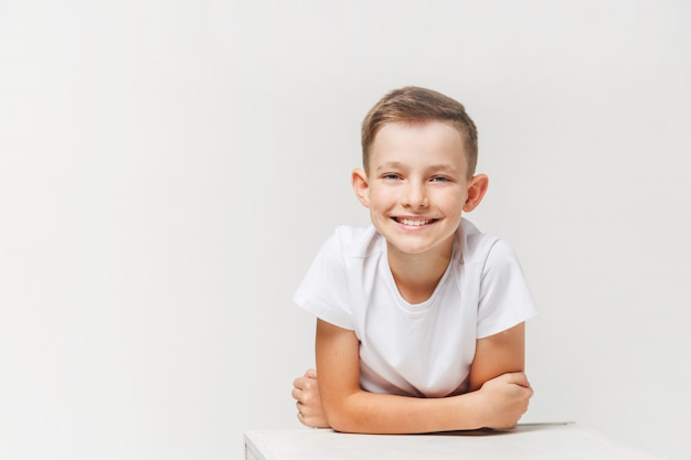 Chiuda sul ritratto dell'adolescente sveglio sorridente dei giovani nel bianco, isolato su bianco