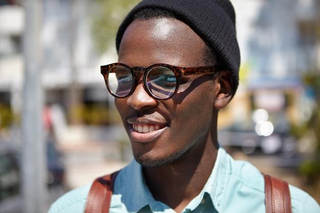 Chiuda sul ritratto dell'estate di giovane studente europeo nero allegro bello in occhiali d'avanguardia e cappello che sorridono felicemente, godendo della mattina soleggiata