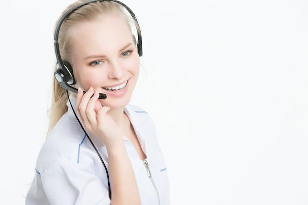 Chiuda sul ritratto dell'operaio di servizio di assistenza al cliente della donna, operatore sorridente della call center con la cuffia avricolare del telefono