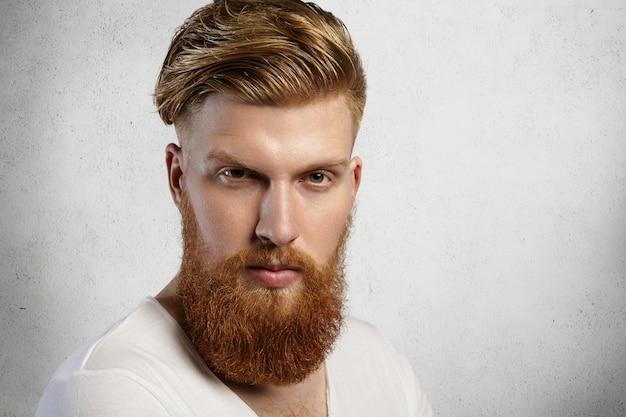 Chiuda sul ritratto dell'uomo alla moda hipster rossa con barba sfocata e taglio di capelli alla moda che indossa la maglietta bianca mentre posa isolata contro il muro con espressione seria o arrabbiata