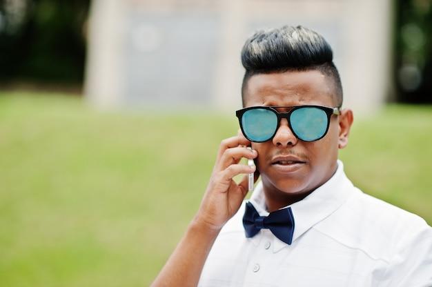 Chiuda sul ritratto dell'uomo arabo alla moda agli occhiali da sole e al farfallino posati all'aperto e parlando sul telefono cellulare. uomo modello arabo.