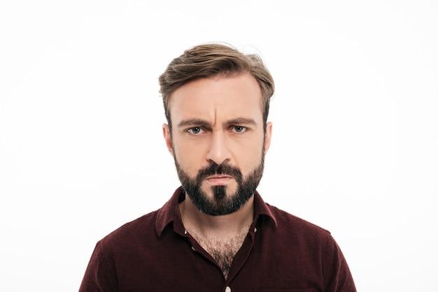 Chiuda sul ritratto dell'uomo barbuto arrabbiato aggrottante le sopracciglia