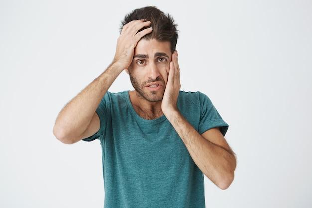 Chiuda sul ritratto dell'uomo barbuto caucasico maturo in maglietta blu, tenendo la mano sulla fronte e sulla guancia che sembrano stanche e annoiate dopo la lunga giornata sul lavoro.
