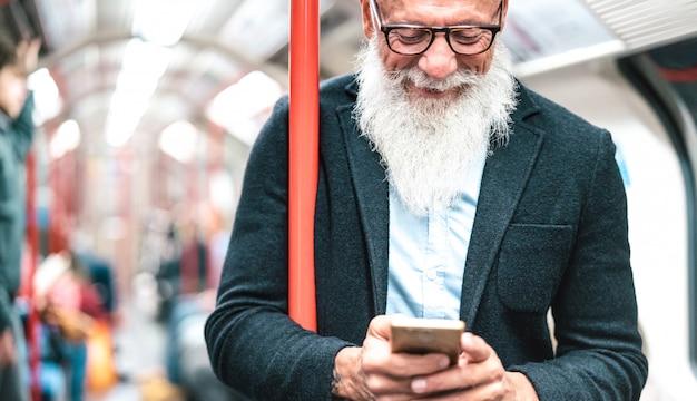 Chiuda sul ritratto dell'uomo barbuto dei pantaloni a vita bassa che utilizza lo smart phone mobile nella metropolitana