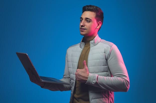 Chiuda sul ritratto dell'uomo caucasico isolato sullo studio blu alla luce al neon